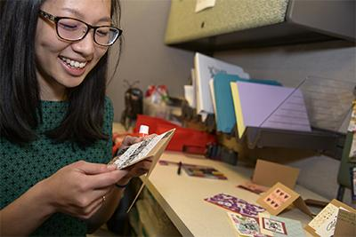 Angela Yung, a data manager for LIvES, puts a personal touch on handmade cards sent to ovarian cancer survivors.