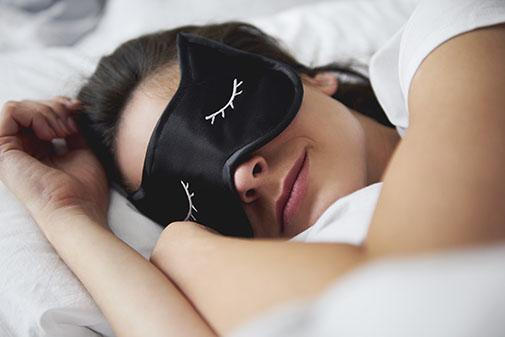 Female in bed wearing a sleep mask
