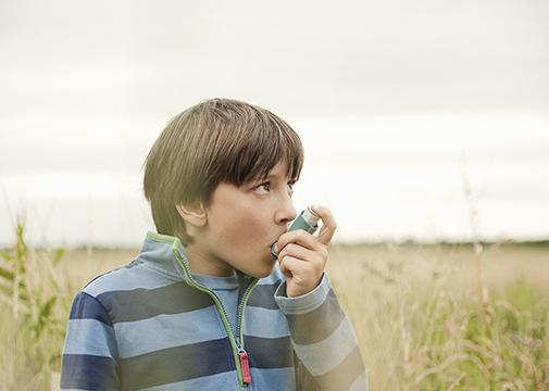 Boy using an inhaler outdoors