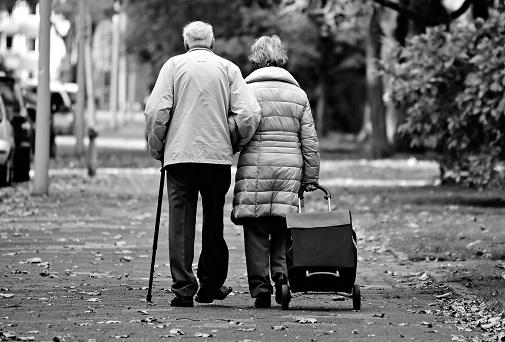 Older couple walking down a sidewalk