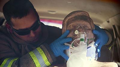 An emergency medical responder with Northwest Fire District practices treating a traumatic brain injury patient using EPIC treatment protocol. (Photo: Bob Demers/UA News)